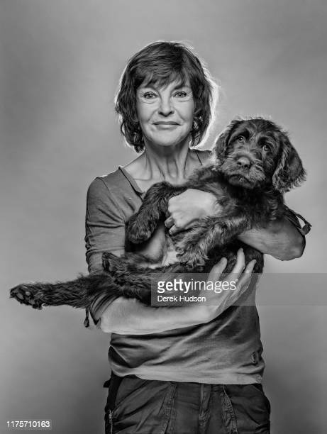 Portrait of German actress Katrin Sass as she poses with her pet dog Lucky in front of a gray background Treptow Berlin Germany August 3 2019