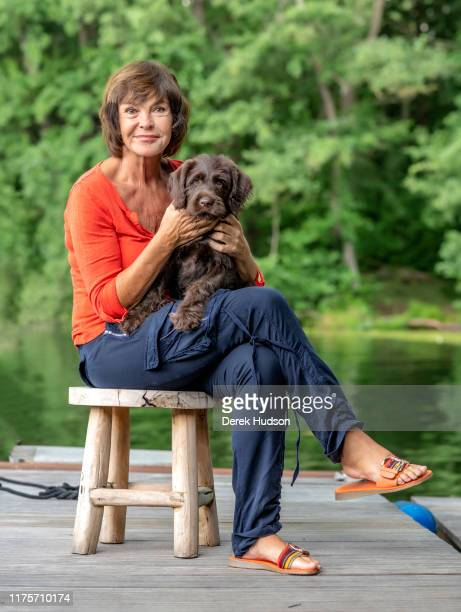 Portrait of German actress Katrin Sass as she poses with her pet dog Lucky on wooden dock Treptow Berlin Germany August 3 2019