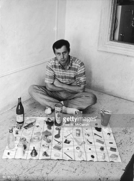 Portrait of German artist Franz Erhard Walther as he sits on the floor in a corner of a room with sixty different ojects layed out in a grad in front...