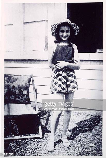Portrait of German Jewish diarist Anne Frank smiling outside the family home wearing a straw hat circa 1940