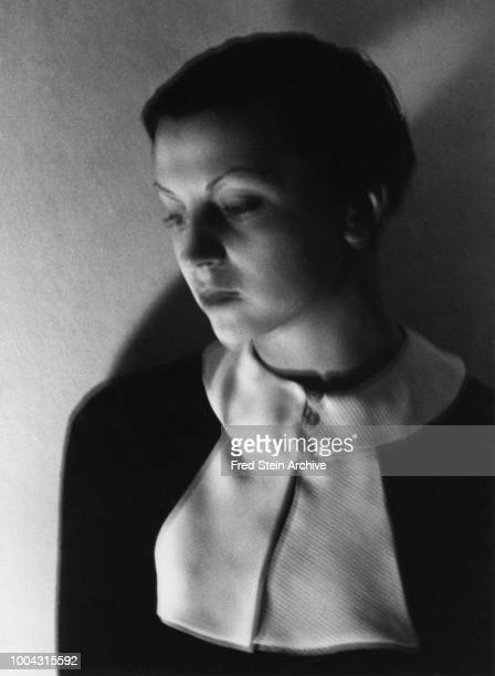 Portrait of German photographer Gerda Taro as she poses lit from below Paris France 1936
