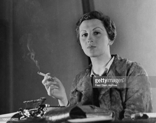Portrait of German photographer Gerda Taro as she smokes a cigarette seated behind a typewriter on a desk Paris France 1936
