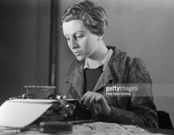 Portrait of German photographer Gerda Taro as she works at a typewriter on a desk Paris France 1936