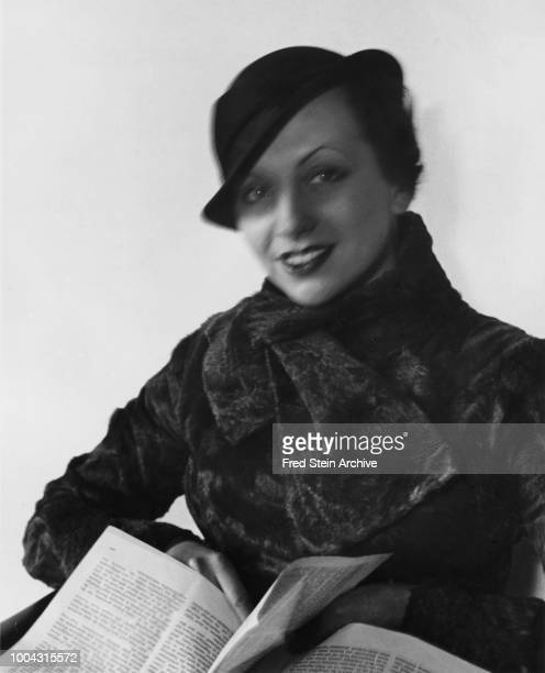 Portrait of German photographer Gerda Taro in a hat and coat as she holds an open text Paris France 1936