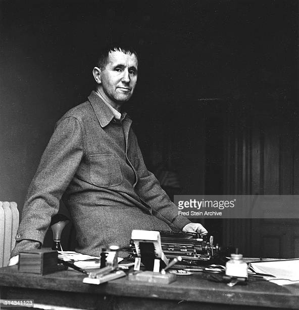 Portrait of German playwright Bertolt Brecht as he sits on a desk twentieth century