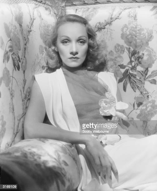 Portrait of German-born actor Marlene Dietrich wearing a sleeveless dress with a chiffon bodice and floral corsage appliques while sitting in an...