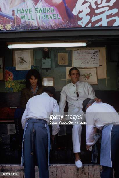 Portrait of Germanborn American fashion designer John Weitz dressed in one of his designs a white suit with toggle fasterners as he sits for a...