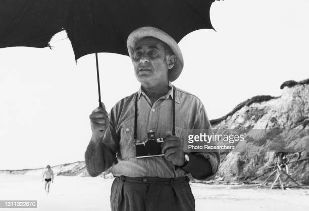 Portrait of German-born American photographer Alfred Eisenstaedt as he holds an umbrella and a camera on a beach, circa 1960s.