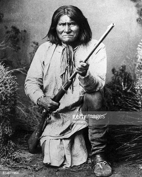 Portrait of Geronimo American Apache chieftain He is kneeling with a rifle in his hands Photograph 1887