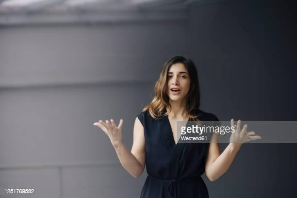 portrait of gesturing young businesswoman against grey background - reden stock-fotos und bilder