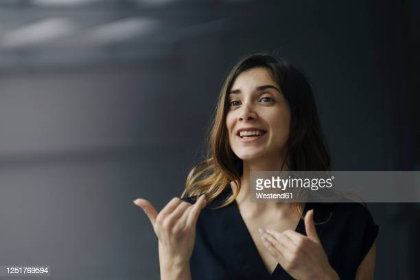 portrait of gesturing young businesswoman against grey background - gesturing stock pictures, royalty-free photos & images