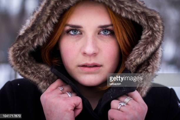 portrait of ginger girl in a coat on a snowy day. - febbraio foto e immagini stock