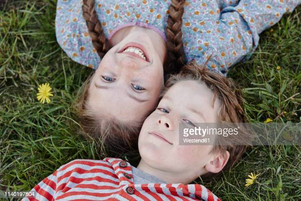 portrait of girl and and her little brother lying head to head on a meadow - nur kinder stock-fotos und bilder