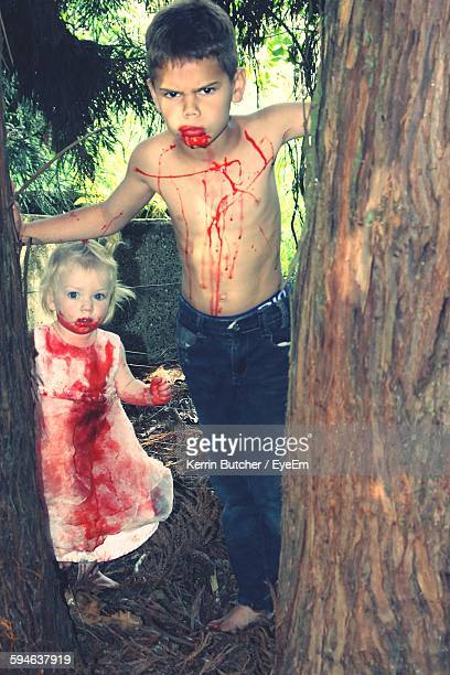 Portrait Of Girl And Boy With Blood Standing On Field