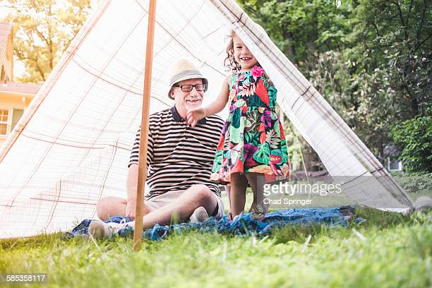 Portrait of girl and grandfather peeking from homemade garden tent