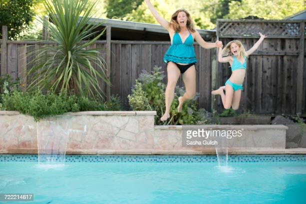 Portrait of girl and mother jumping into outdoor swimming pool