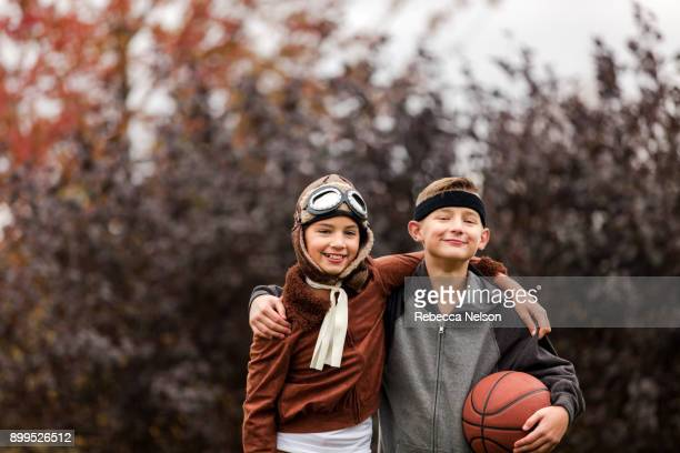 Portrait of girl and twin brother wearing basketball player and pilot costumes for halloween in park