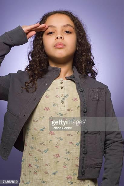 Portrait of girl (10-11) arm raised, saluting