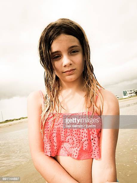 Portrait Of Girl At Beach Against Cloudy Sky