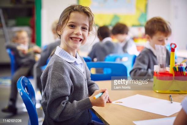 portrait of girl at desk in elementary school - primary school child stock pictures, royalty-free photos & images