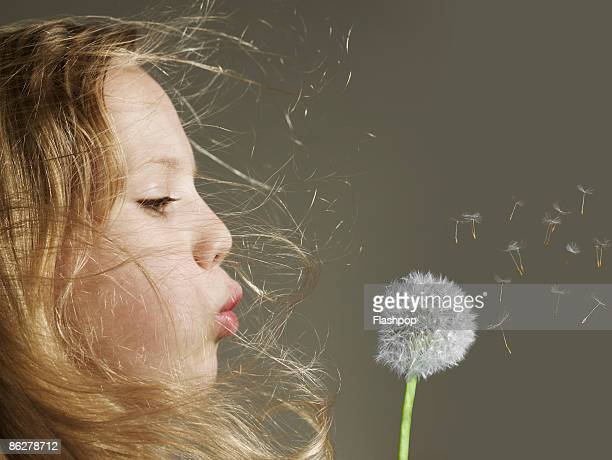 Portrait of girl blowing a dandelion head