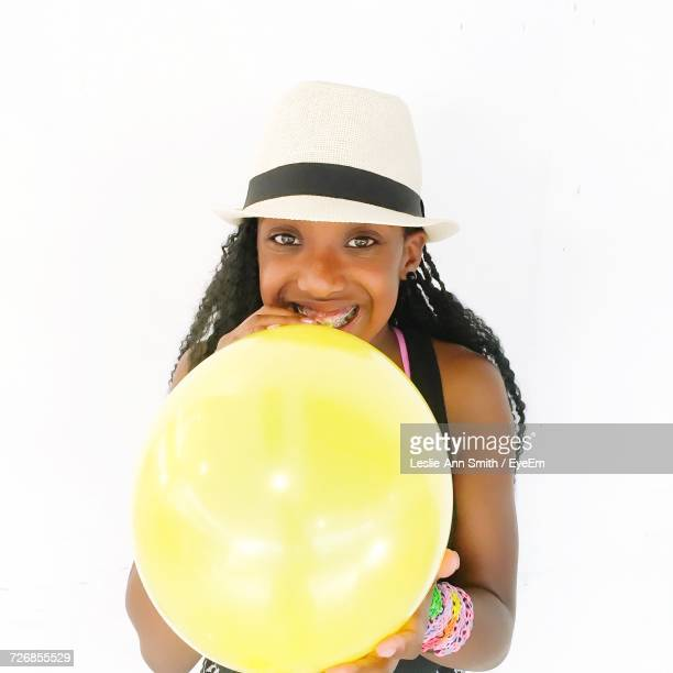 Portrait Of Girl Blowing Balloon Against White Background