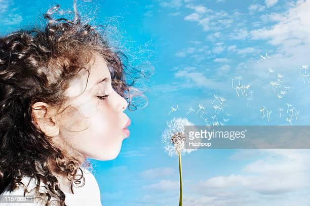 Portrait of girl blowing dandelion clock