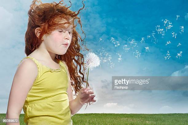 portrait of girl blowing dandelion clock - redhead stock pictures, royalty-free photos & images