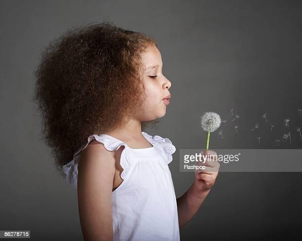 Portrait of girl blowing dandelion head