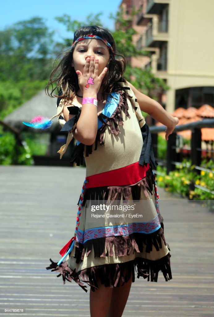 Portrait Of Girl Blowing Kiss While Standing On Boardwalk Against Trees : Stock Photo