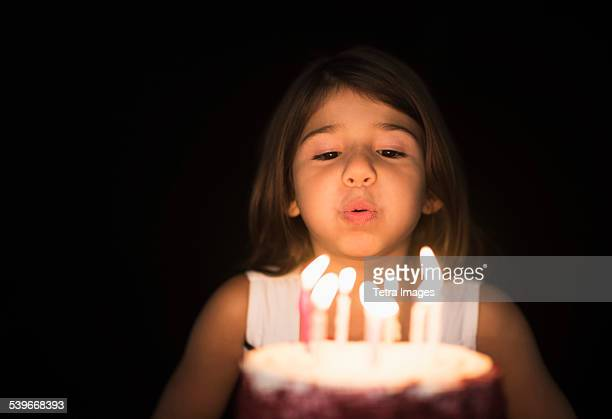 Portrait of girl (6-7) blowing out birthday candles