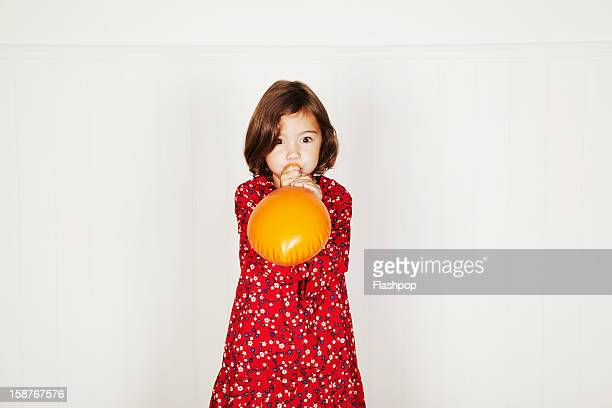 Portrait of girl blowing up balloon