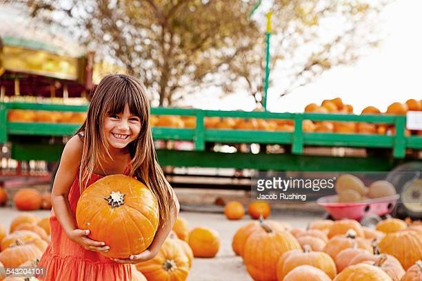 Portrait of girl carrying pumpkin in farmyard