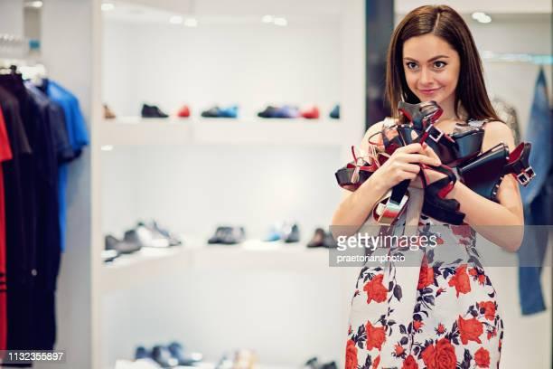 portret van meisje kiezen schoenen in een boetiek - nette schoen stockfoto's en -beelden