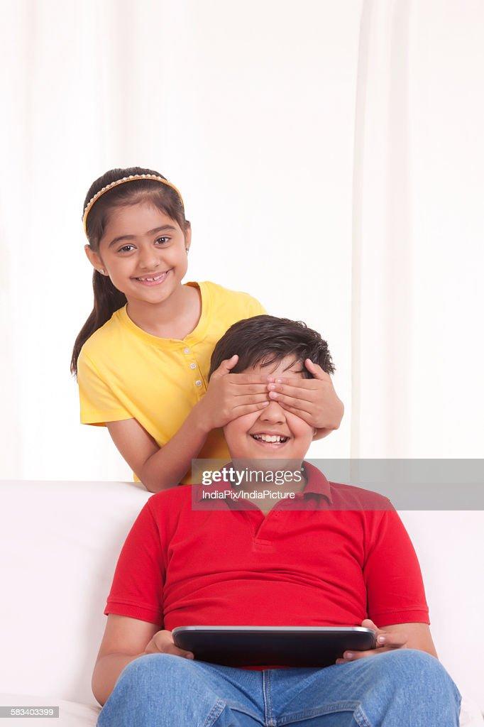 Portrait of girl covering boys eyes : Stock Photo