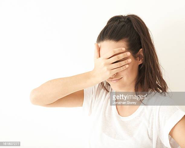 Portrait of girl covering her eyes with her hand