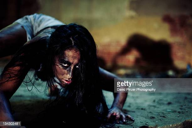 portrait of girl crawling on ground - horror movie stock photos and pictures