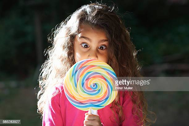 portrait of girl crossing eyes with lollipop in front of her face in garden - cross eyed stock pictures, royalty-free photos & images