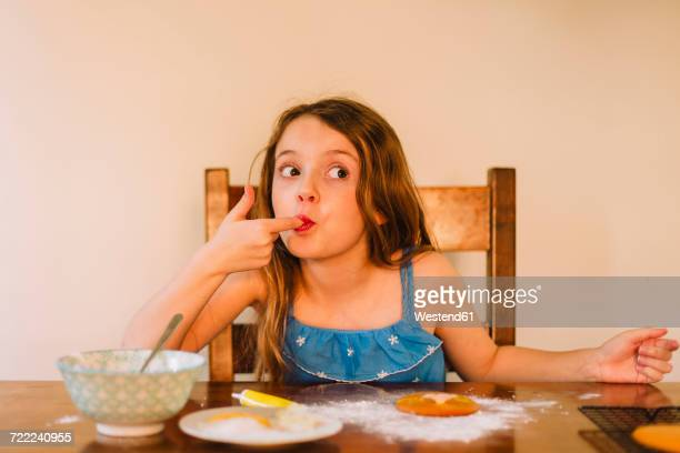 Portrait of girl decorating biscuits at home