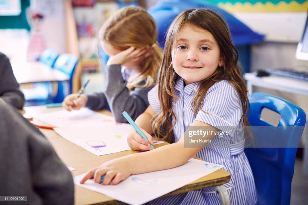 Portrait of girl drawing at desk in elementary school : Stock-Foto