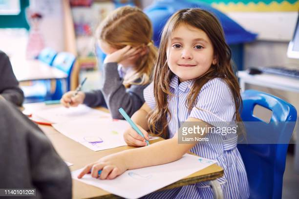 portrait of girl drawing at desk in elementary school - schulgebäude stock-fotos und bilder