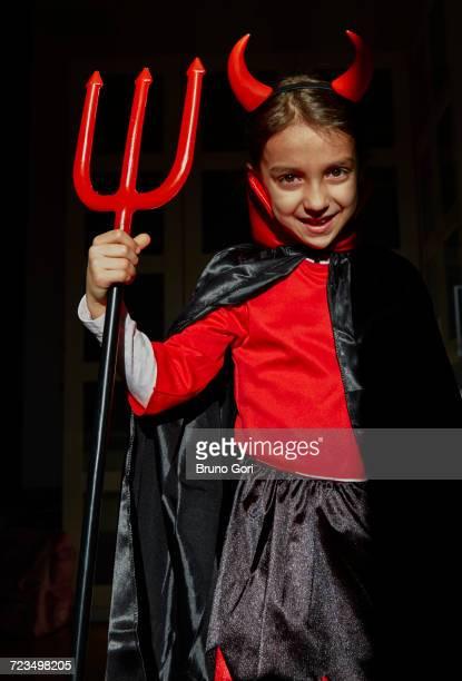 portrait of girl dressed up as a devil holding a devils fork - disfraz de diablo fotografías e imágenes de stock
