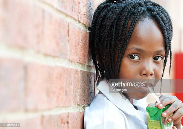 portrait of girl drinking juice through straw outside school, johannesburg, gauteng province, south africa - juice carton stock photos and pictures