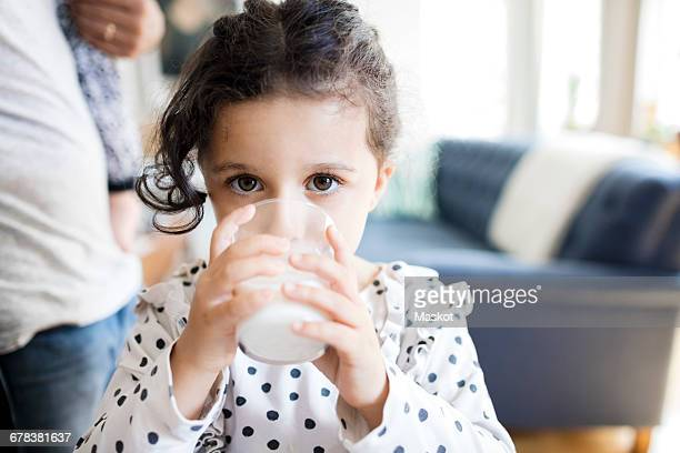 portrait of girl drinking milk while father standing in background - milk stock pictures, royalty-free photos & images