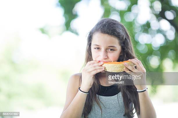 Portrait of girl eating a melon