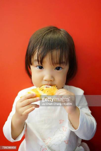 Portrait Of Girl Eating Bread Omelet Against Red Background