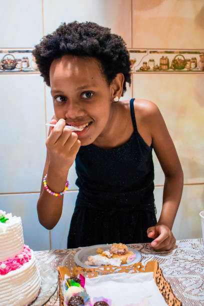 Portrait Of Girl Eating Food Standing At Home