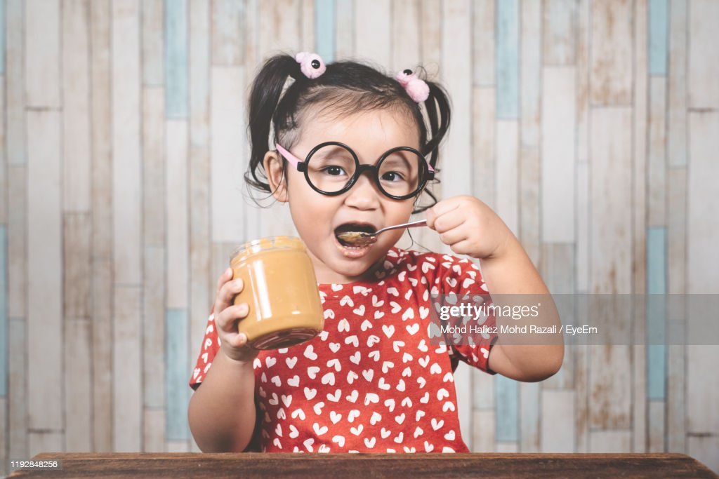 Portrait Of Girl Eating Peanut Butter At Table Against Wall : Stock Photo