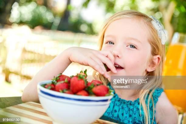 Portrait of girl eating stawberries