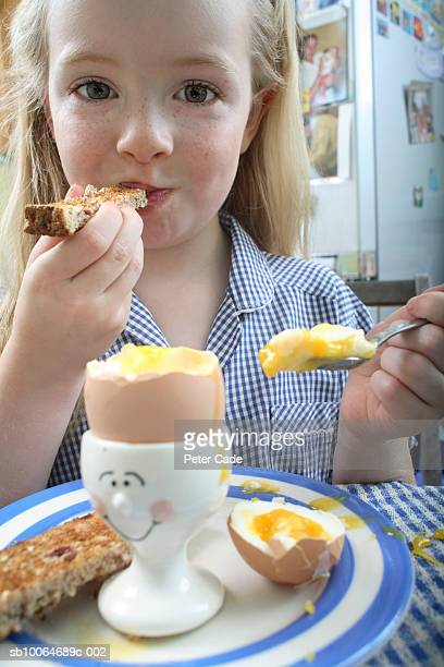 Portrait of girl (4-6) eating toast and hard boiled egg